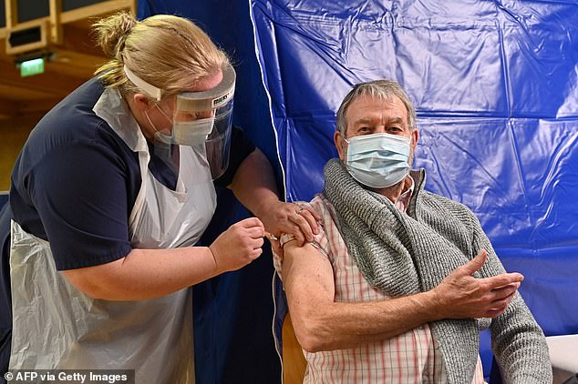 Some places have already vaccinated almost all their over-80s. Above is a patient receiving the vaccine at the Bournemouth International Centre yesterday