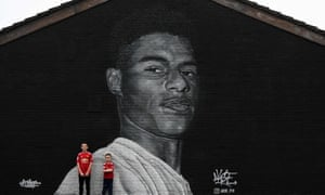 Children in Manchester United shirts pose against a mural of Marcus Rashford in Withington, Manchester by graffiti artist Akse P19