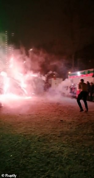 A stream of red light erupts from the fireworks during the dangerous 'duel'