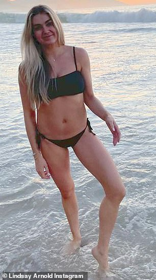 Beach babe:The toned star looked slender with a small waistline as she wore a black bikini with her blonde hair down over her shoulders