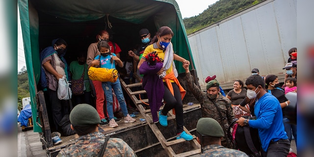 A Honduran migrant woman is helped off a Guatemalan army truck after being returned to El Florido, Guatemala, one of the border points between Guatemala and Honduras, Tuesday, Jan. 19, 2021. (AP Photo/Oliver de Ros)