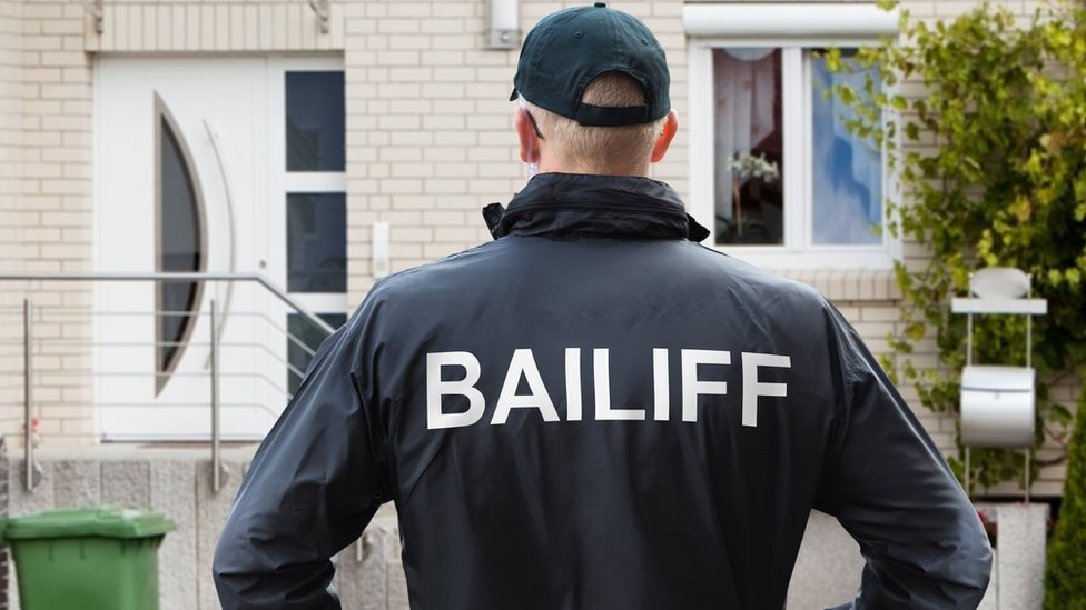 Bailiff stands in front of house