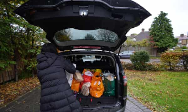 A volunteer loads food parcels into a car in London in October 2020
