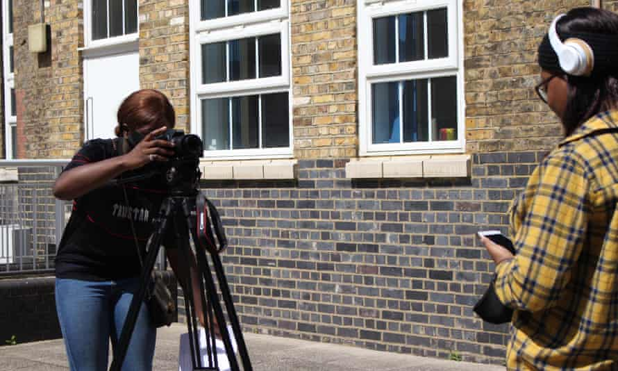 Two young women, one behind a camera, the other presenting to camera; both part of a summer school run by Ghetto Film School last year.