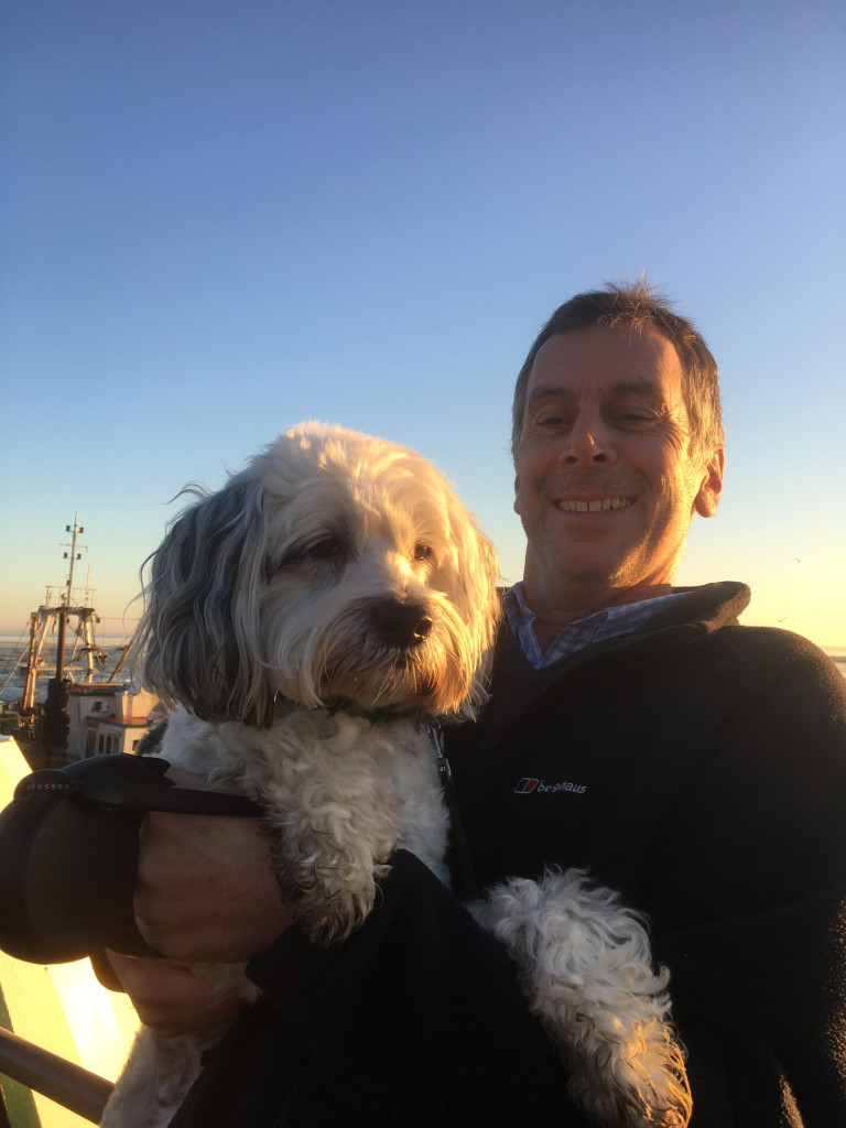 An outside pic of Mike holding his dog Alfie