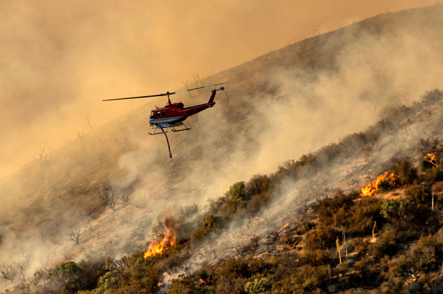 A helicopter prepares to drop water on the Lake Fire burning in the Angeles National Forest north of Santa Clarita, Calif., on Thursday, Aug. 13, 2020. (AP Photo/Noah Berger)