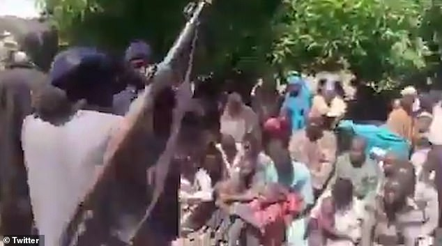 Footage shared online purportedly shows the kidnappers brandishing AK-47s and a rocket launcher in front of the children who can be heard wailing as the men yell 'Allahu akbar' and fire shots into the air.