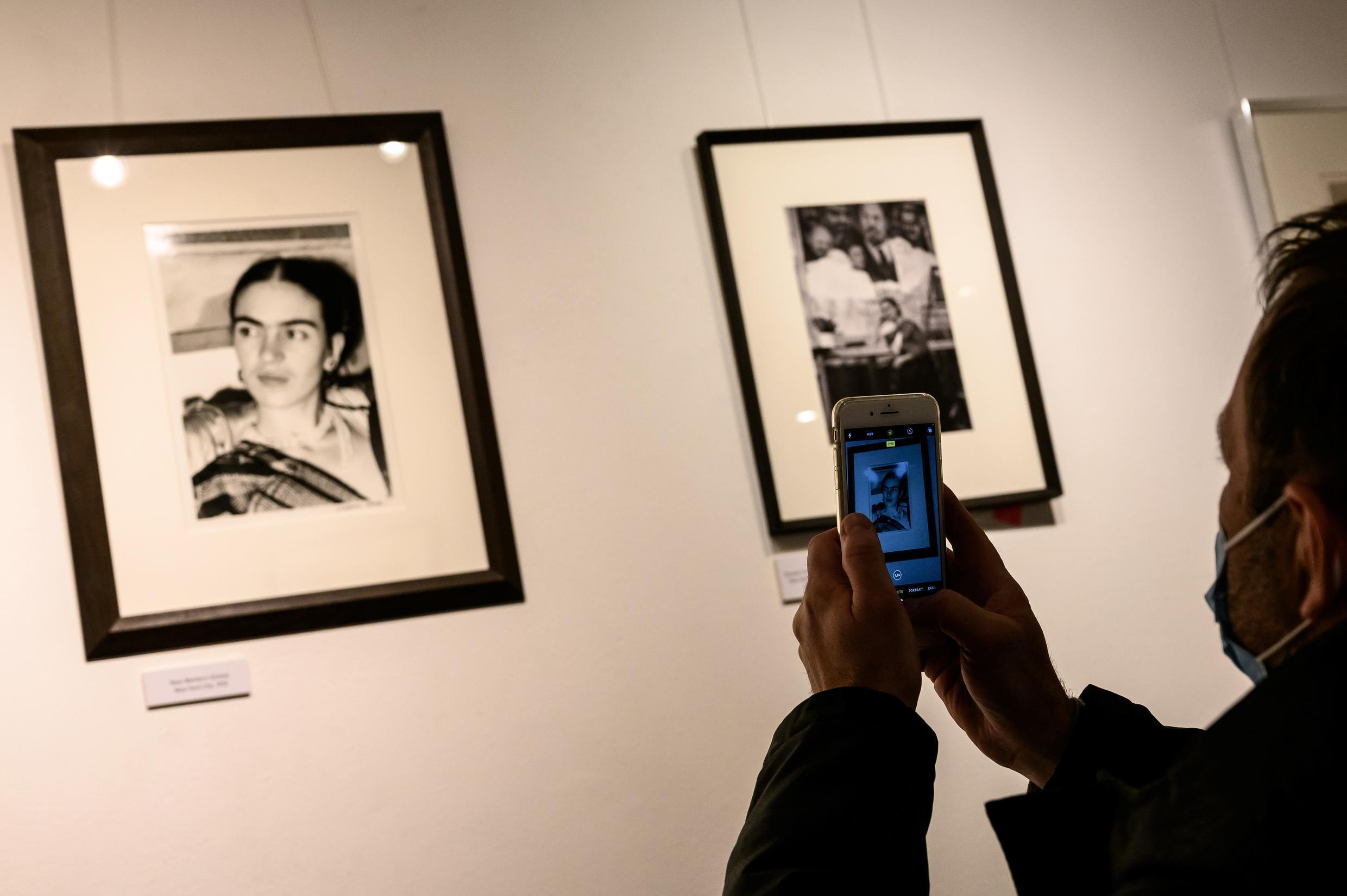 """A man looks at pictures by US artist Lucienne Bloch showing Mexican artist Frida Kahlo displayed as part of the exhibition entitled """"The artist's vision"""" on February 6, 2021, in the """"Galerie de l'instant"""" in Paris."""