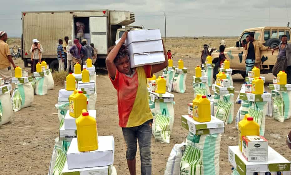 People displaced by conflict receive food aid donated by a Kuwaiti charity organisation in the village of Hays, near the conflict zone in Yemen's western province of Hodeida, this week.