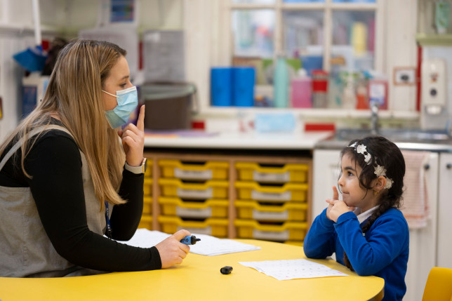 CARDIFF, WALES - FEBRUARY 23: A teacher wearing a face mask teaches a child at Roath Park Primary School on February 23, 2021 in Cardiff, Wales. Children aged three to seven began a phased return to school on Monday. Wales' education minister Kirsty Williams has said more primary school children will be able to return to face-to-face learning from March 15 if coronavirus cases continue to fall. (Photo by Matthew Horwood/Getty Images)
