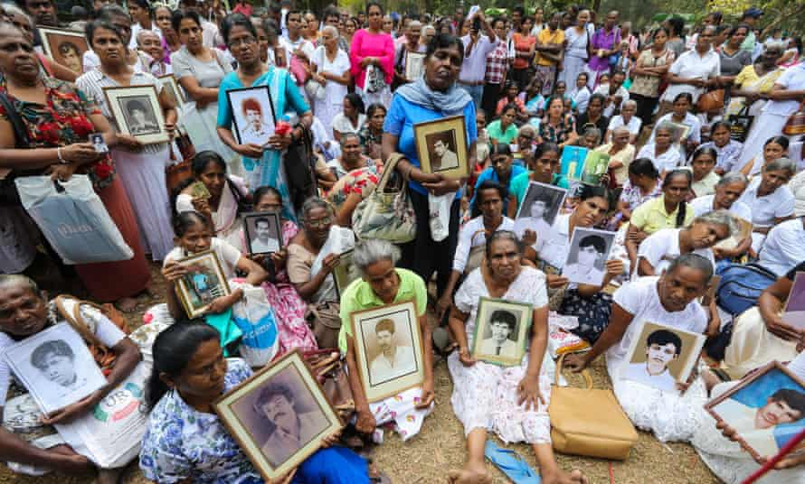 Sri Lankans hold portraits of relatives who disappeared during a protest to demand an investigation, in Colombo, on 14 February 2020.