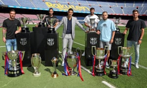 Luis Suárez (centre) poses with Lionel Messi (left), Sergio Busquets (second left), Gerard Piqué (third right), Jordi Alba and Sergi Roberto (right) as well as some of the trophies he won during his six years at Barcelona.