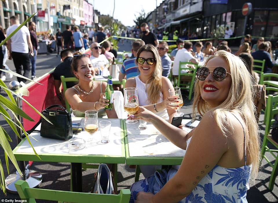 Women pose for a photo at an outdoor dining area on Northcote Road in Battersea, London on September 13, 2020