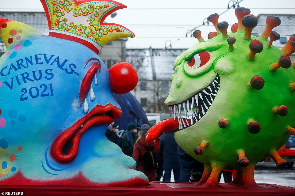 A cartoonish coronavirus confronts a jester depicting the Rosenmontag carnival as organisers were forced to abandon plans for their usual festivities
