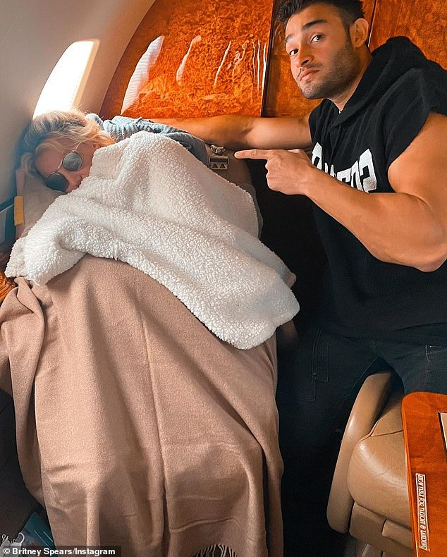 Snooze: Spears enjoyed a mini-nap on the plane posed next to her boyfriend