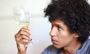 Man holding a glass of white wine looking at the quality of the wine in the glass