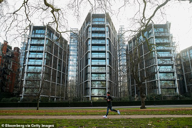 A jogger passes One Hyde Park, a luxury residential and retail complex, in Knightsbridge. A new report shows that 874,354 people in London have assets, including property, worth more than £720,000