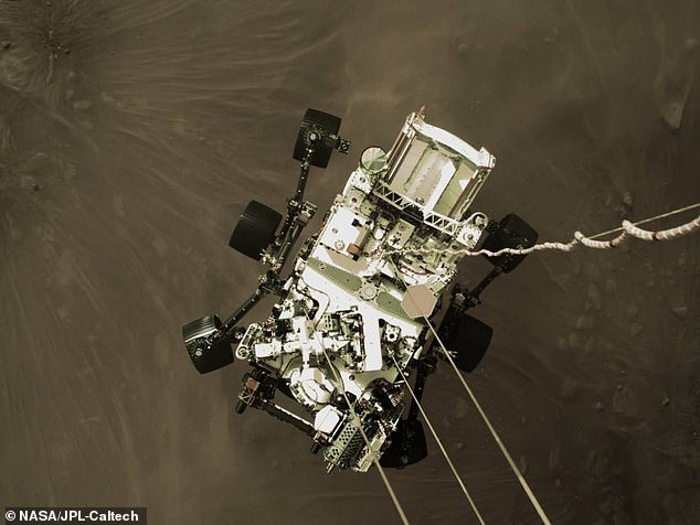 Pictured is an image snapped by the sky crane as it lowered NASA's Perseverance down to Mars' surface using long mechanical bridles