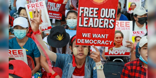 Anti-coup protesters display images of deposed leader Aung San Suu Kyi in Yangon, Burma, on Thursday. (AP Photo)