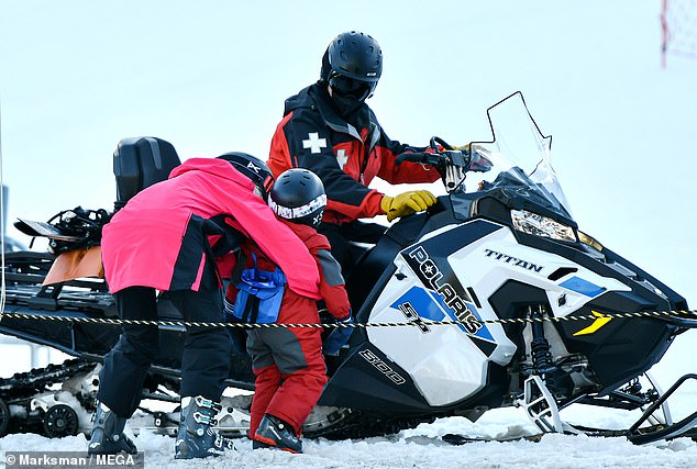 Doting mom:Heidi escorted her son away from the speeding skiers to catch a safe ride from a snow mobile