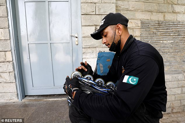 Pictured:A Special Security Unit (SSU) police member checks his rollerblade after a practice session at the headquarters in Karachi, Pakistan February 18