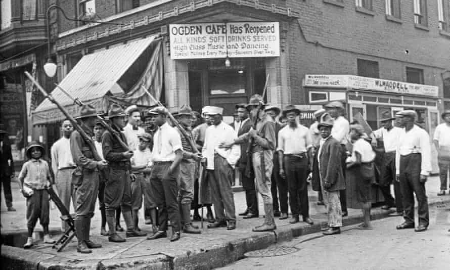 Black citizens and armed National Guard stand in front of a cafe during race riots in Chicago in the 'red summer' of 1919.