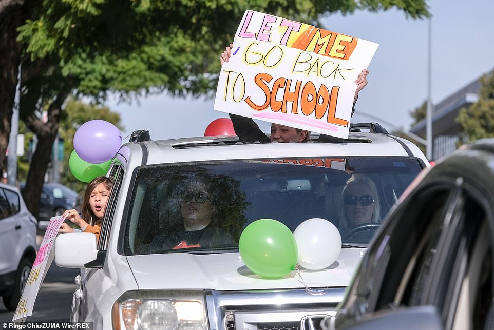 Students and parents holding placards in their car protest during a car rally to encourage Los Angeles County to reopen schools