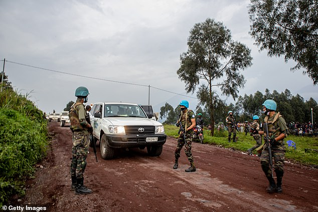 UN peacekeepers and Congolese armed forces stand near an ambulance transporting a victim from the site where Italian Ambassador Luca Attanasio was fatally attacked when the convoy he was traveling in came under attack on February 22, 2021