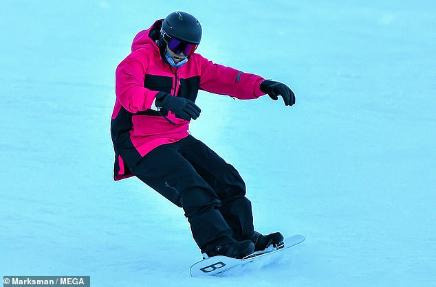 Making moves: 37-year-old Spencer looked focused as he sped down the hill on his white Burton brand snowboard