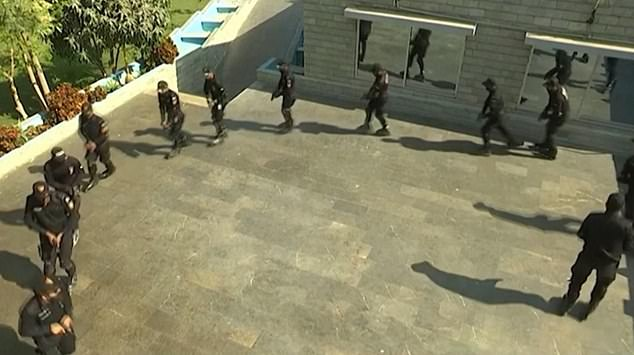 Pictured: A still from a video showing the roller-cops gliding in a circle while holding pistols