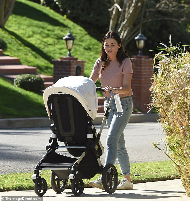 Carting along: Jenna pushed her son's stroller along and kept her white disposable face mask strapped around her wrist