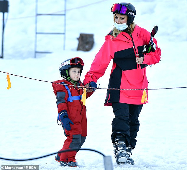 Helping hand: The 34-year-old reality star held son Gunner's hand clad in a pink-and-black snowsuit as they pair made their way through the snow