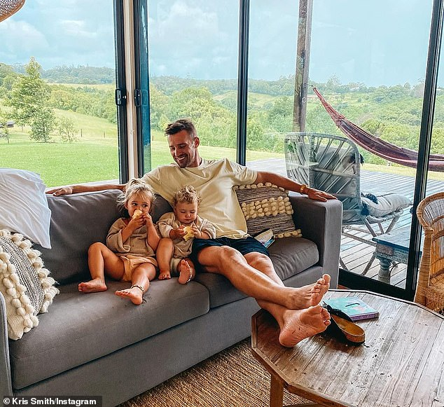 Relaxed: On Wednesday, he shared a picture showing himself beaming on the couch with his little girls sitting beside him as they ate their food