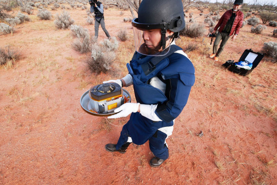 In this handout image from Japan Aerospace Exploration Agency (JAXA), a member of JAXA collects Hayabusa2's capsule carrying the first extensive samples of an asteroid after it landed in the Woomera restricted area, Australia, December 6, 2020. Japan Aerospace Exploration Agency (JAXA)/Handout via Reuters THIS IMAGE WAS PROVIDED BY A THIRD PARTY. NO ARCHIVES. NO RESALES.