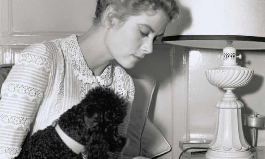 Grace Kelly, primly dressed and reading a script with her black French poodle tucked under her arm