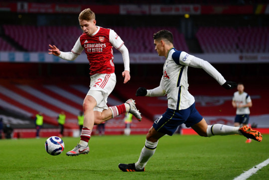 Emile Smith Rowe of Arsenal controls the ball whilst under pressure from Erik Lamela of Tottenham Hotspur during the Premier League match between Arsenal and Tottenham Hotspur at Emirates Stadium on March 14, 2021 in London, England. Sporting stadiums around the UK remain under strict restrictions due to the Coronavirus Pandemic as Government social distancing laws prohibit fans inside venues resulting in games being played behind closed doors.