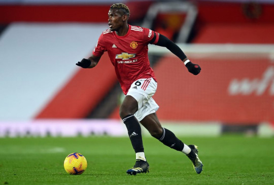 Manchester United's French midfielder Paul Pogba runs with the ball during the English Premier League football match between Manchester United and Everton at Old Trafford in Manchester, north west England, on February 6, 2021.