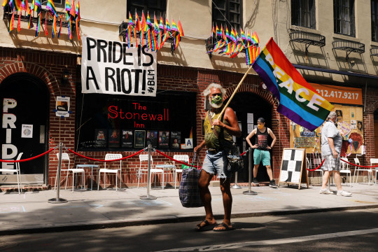 People walk by the Stonewall Inn, an iconic bar for the LGBTQ community around the world, on June 25, 2020 in New York City.