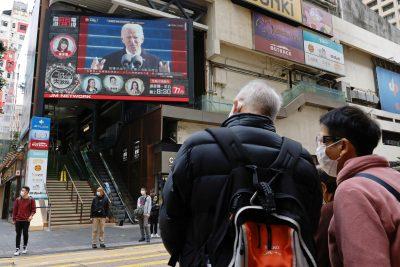 People look at a TV screen showing news of US President Joe Biden after his inauguration, in Hong Kong, China, 21 January 2021 (Photo: Reuters/Tyrone Siu).