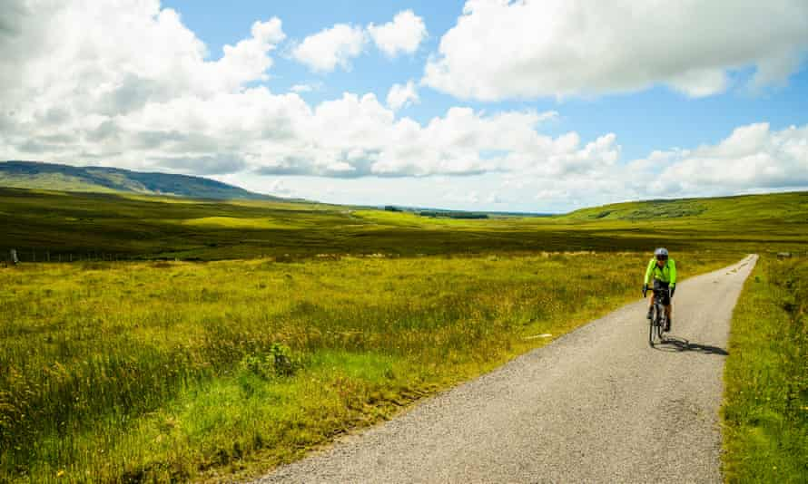 Female cyclist on empty road on the island of Islay Scotland