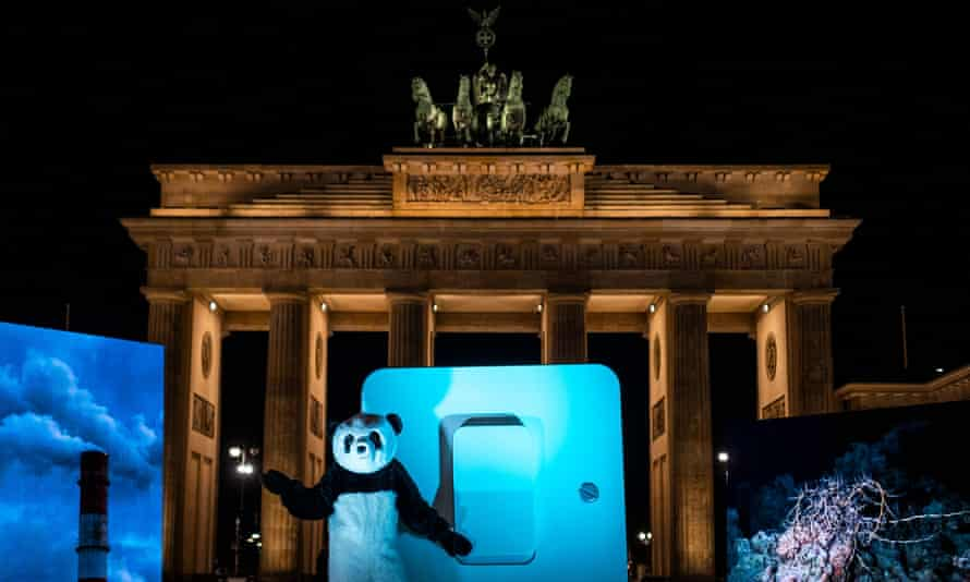 A WWF activist dressed in a Panda suit prepares to symbolically throw a giant switch to turn off the illumination of Berlin's Brandenburg Gate.