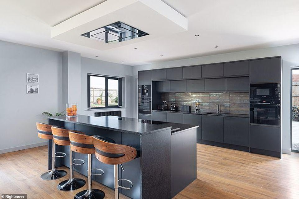 Chic: Suitable for sociable individuals, the Crown Imperial-bespoke kitchen features trendy stools by the island, while the appliances and worktops follow a black scheme