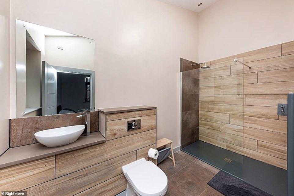 Differences: While the black colour scheme is maintained, wooden flooring is incorporated into another wash area