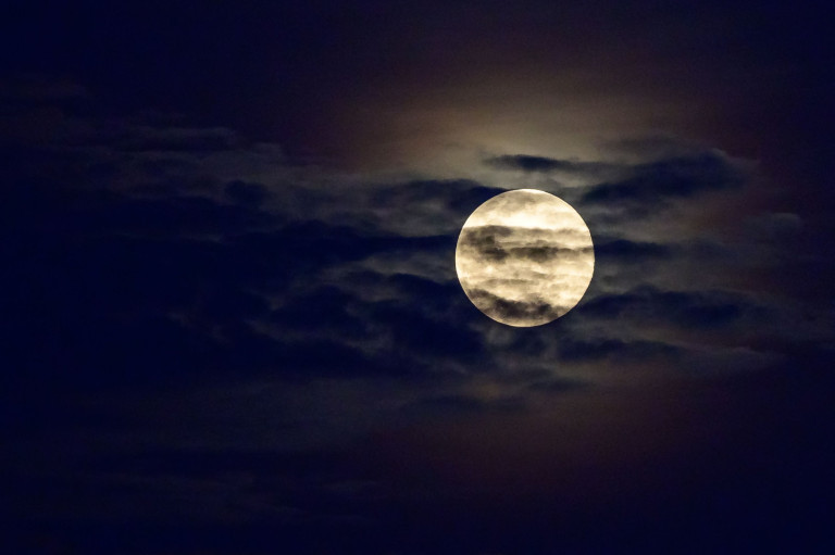 The full Worm Moon is seen behind the clouds in the sky over Bangkok on March 28, 2021. (Photo by Mladen ANTONOV / AFP) (Photo by MLADEN ANTONOV/AFP via Getty Images)