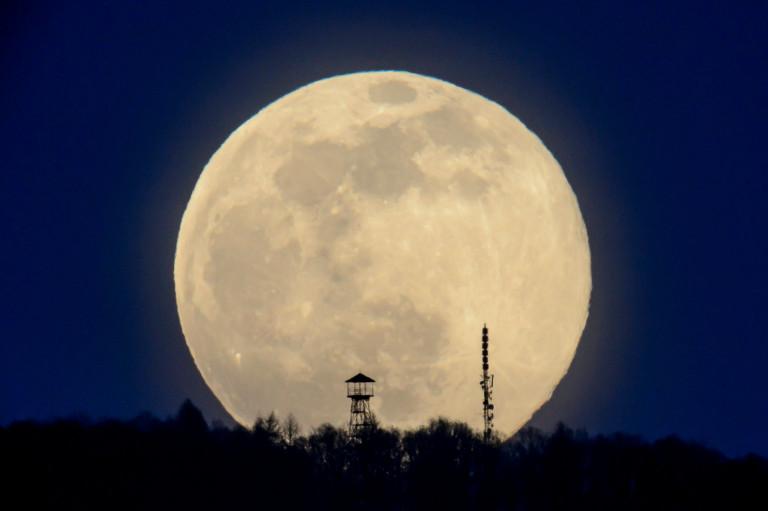 epa09103901 The full moon rises above the Karancs Hills pictured from Karancskeszi, Hungary, 28 March 2021. EPA/Peter Komka HUNGARY OUT