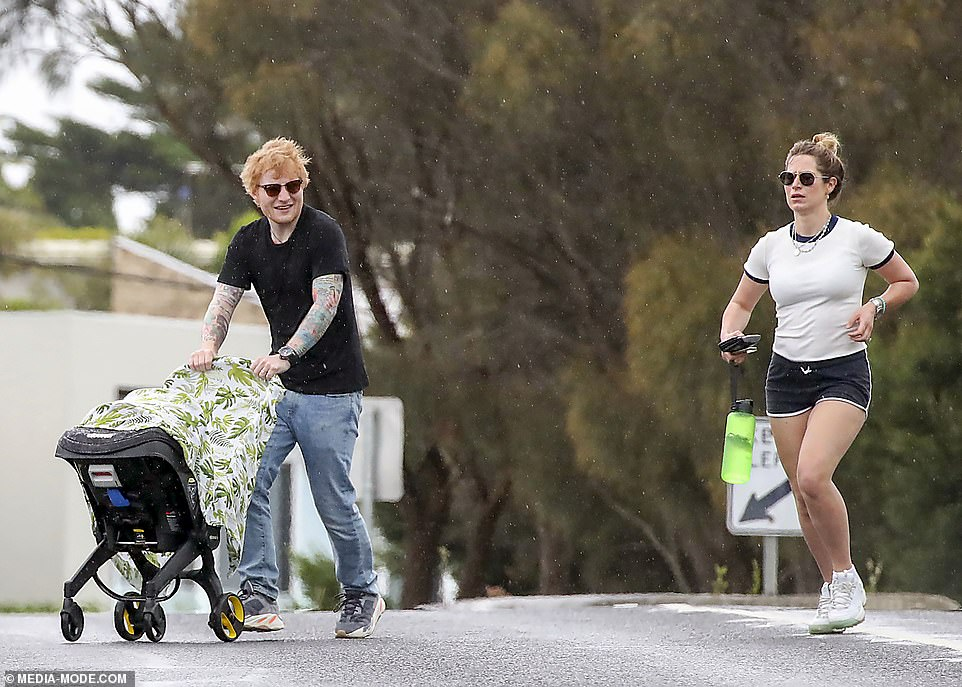 Wet wet wet: With Ed taking over wheeling the pram, the couple made their way home