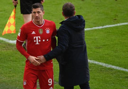 Bayern Munich's German head coach Hans-Dieter Flick greets Bayern Munich's Polish forward Robert Lewandowski during the German first division Bundesliga football match between FC Bayern Munich and VfB Stuttgart in Munich, southern Germany, on March 20, 2021.