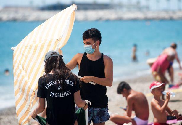 A man wearing a face mask opening an umbrella on the beach