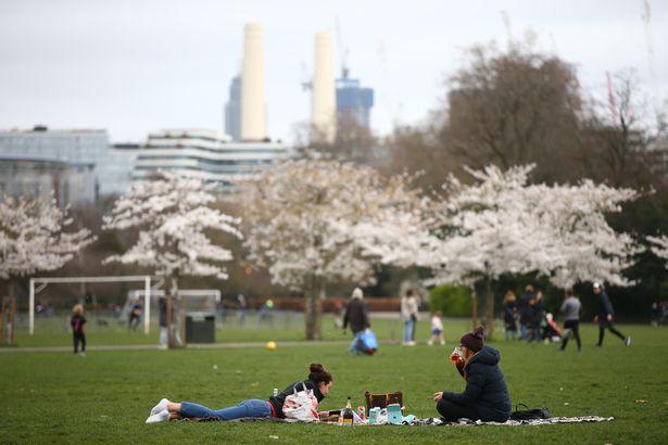 People sit in Battersea Park on March 28, 2021