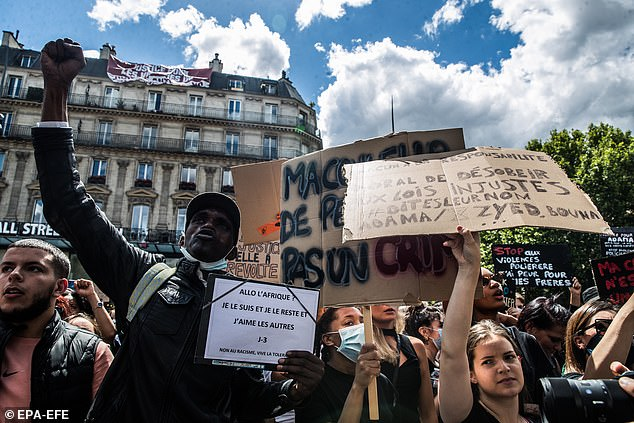 Protesters are carrying signs during a demonstration against racism and police brutality at Republique Square in Paris in June